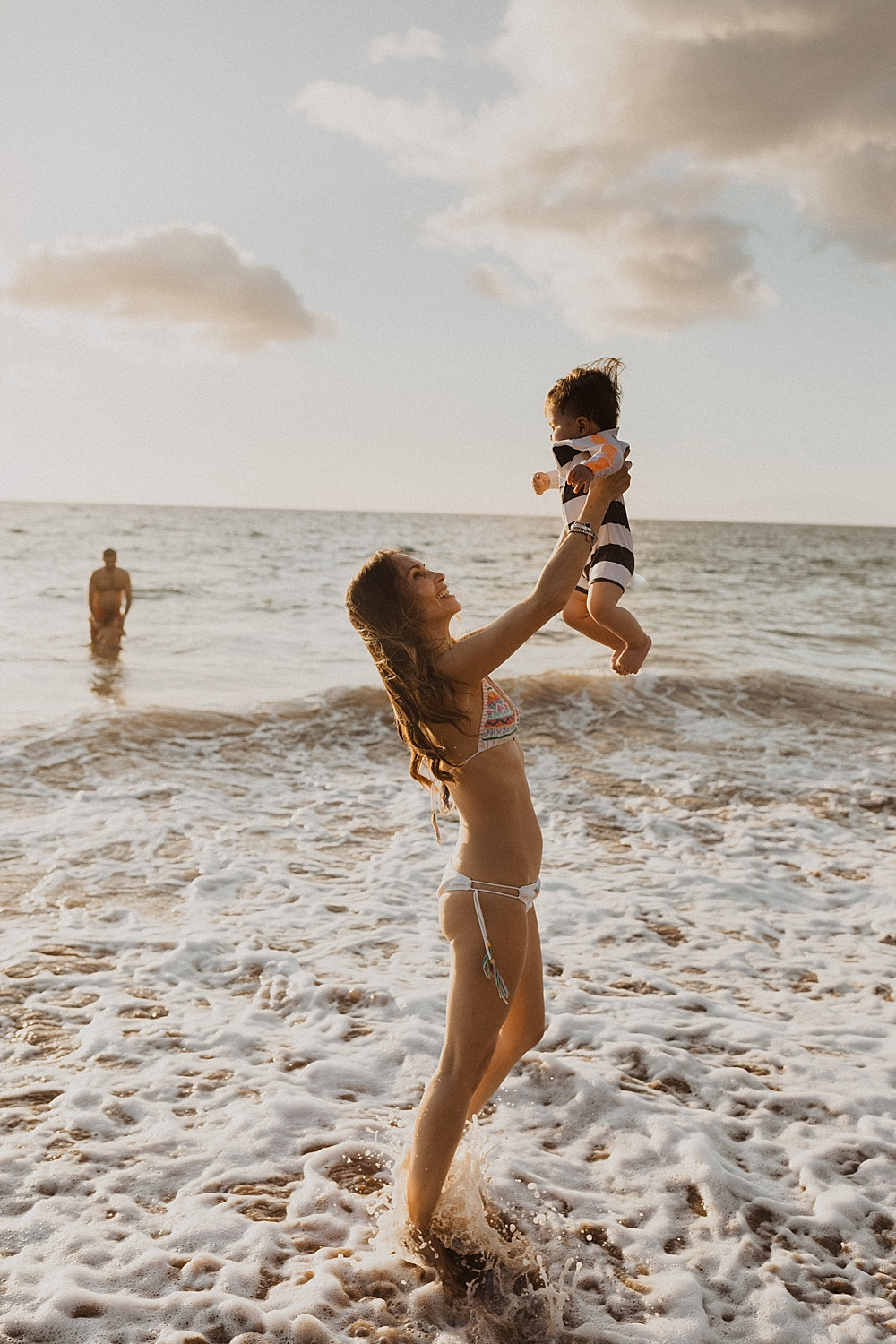 mom throwing son in air during her family photo session on Maui